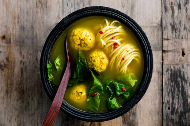 Turmeric Broth With Chicken And Ginger Dumplings. Bowl of turmeric broth with chicken and ginger dumplings