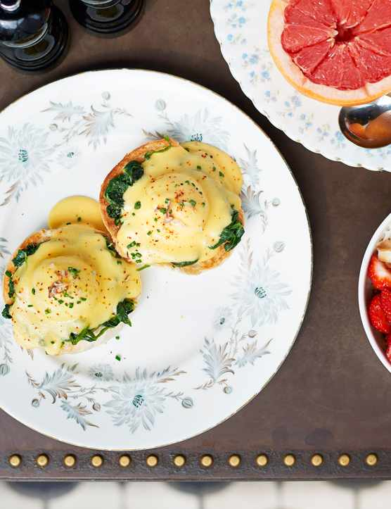 Eggs with Hollandaise sauce on a plate next to a plate of half grapefruit and a bowl of strawberries and banana