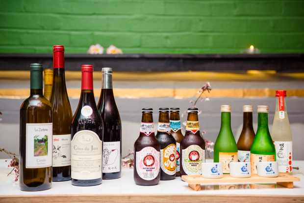 Bottles of wine, beers and sake in front of a green background