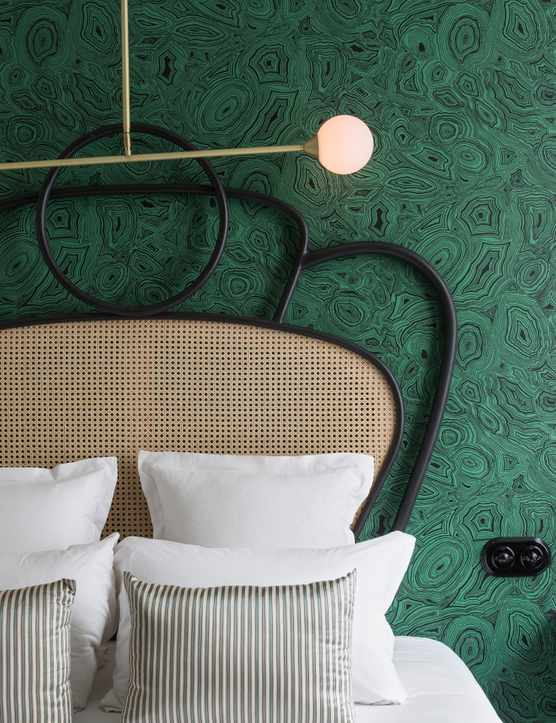 Bed against a green wall at Hotel Panache Pigalle Paris