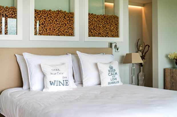 White bed with headboard filled with corks Tinwood Estate Lodges, Chichester
