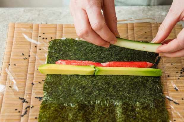 Step 5: Lining the avocado, crabstick and cucumber on the nori