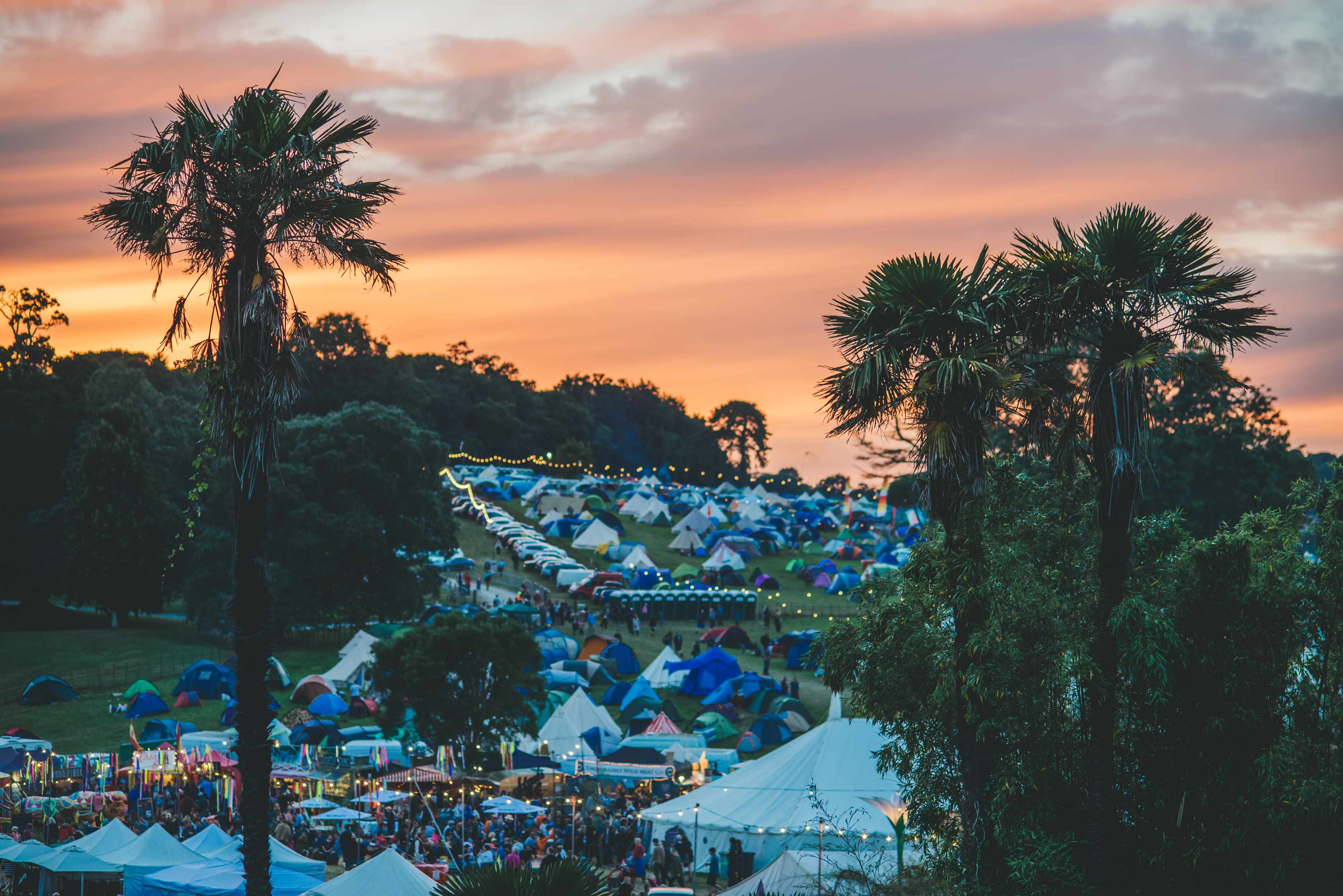 An orange sunset over Port Eliot Festival with tents in the image