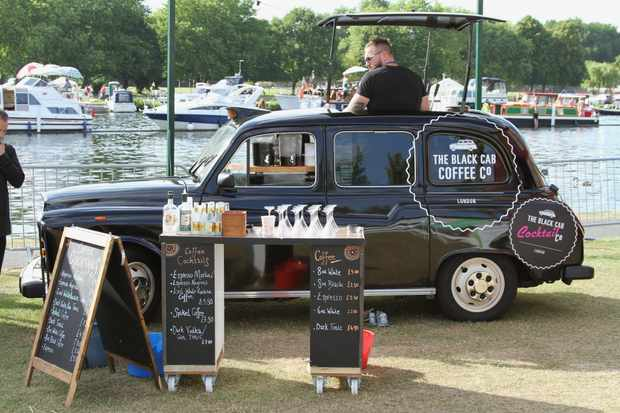 A London black cab is parked next to a lake at Henley festival with a blackboard listing coffees and coffee cocktails