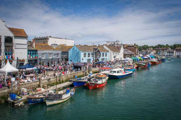 The harbour in Dorset at Pommery Seafood Festival. The teal river has boats on it and colourful houses in the background