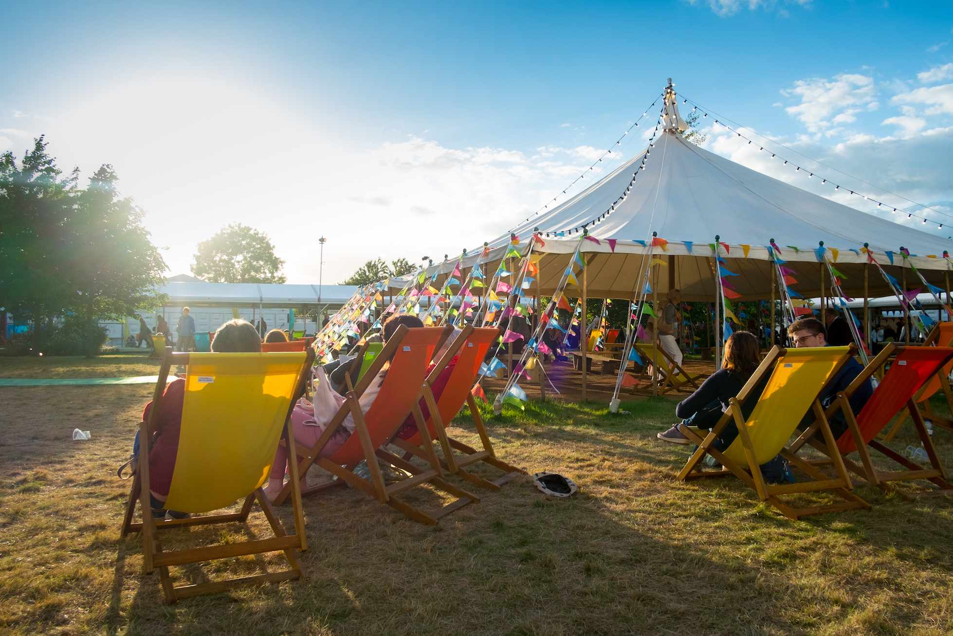 Hay Festival, deckchairs on the grass with large tent in the background