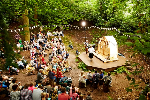 A wooden stage with a performance taking place in a forest is surrounded by people at Timber festival