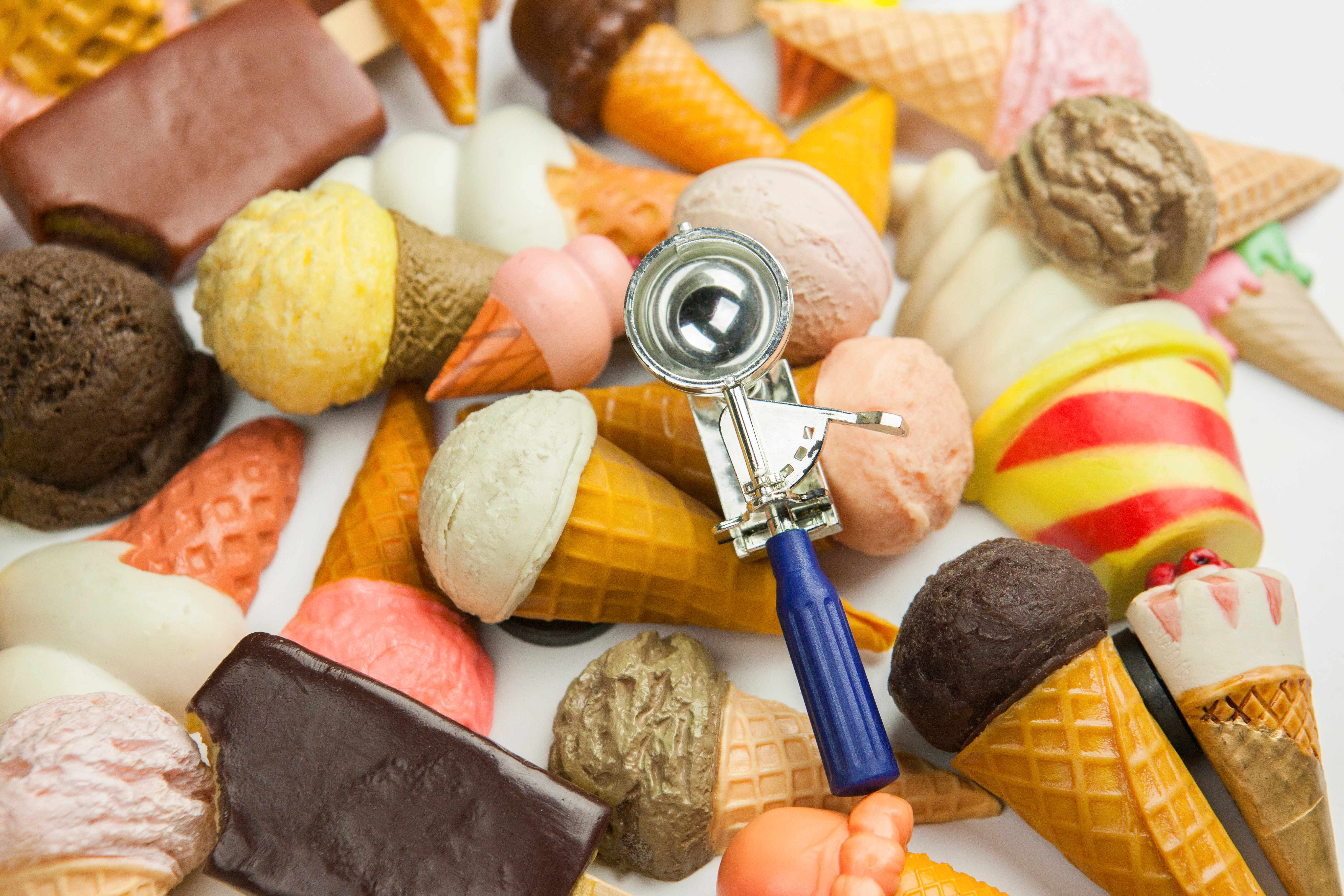 A selection of plastic ice cream cones with an ice cream scoop on top