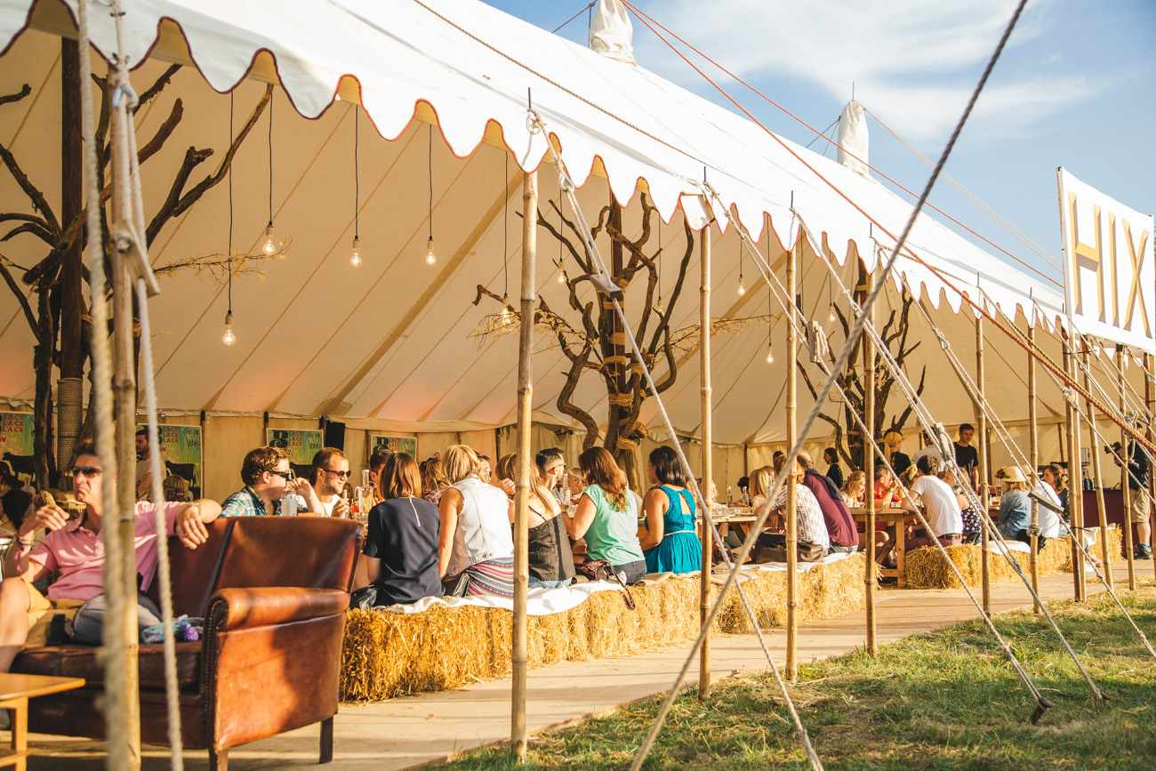 People sat on hay bails in a tent at Wilderness festival