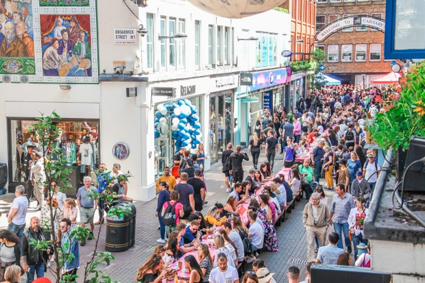 Carnaby Street Eat festival. A long table runs down Carnaby Street with people sat at it eating