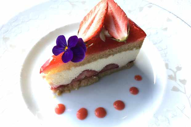 A slice of strawberry cake at Le Viscos decorated with strawberries and edible flowers