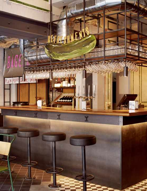 Interior of Monty's Deli - brown wooden tables, tiled floor, bar with stools and giant gherkin handing overhead