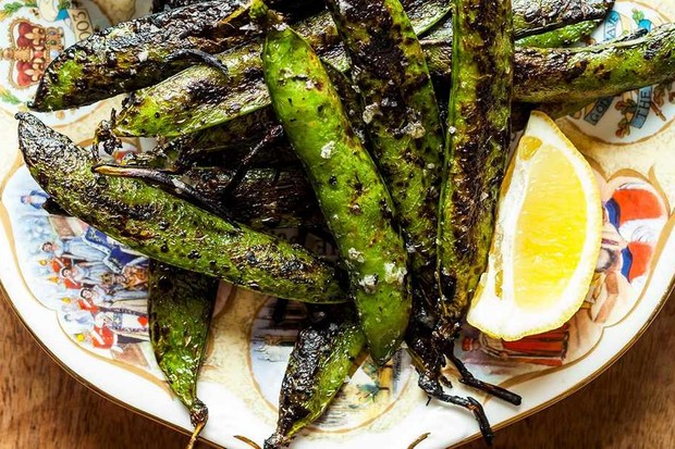 Grilled pea pods on plate with slice of lemon