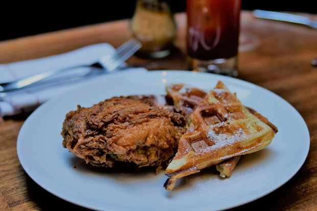 A white plate with fried chicken and waffles