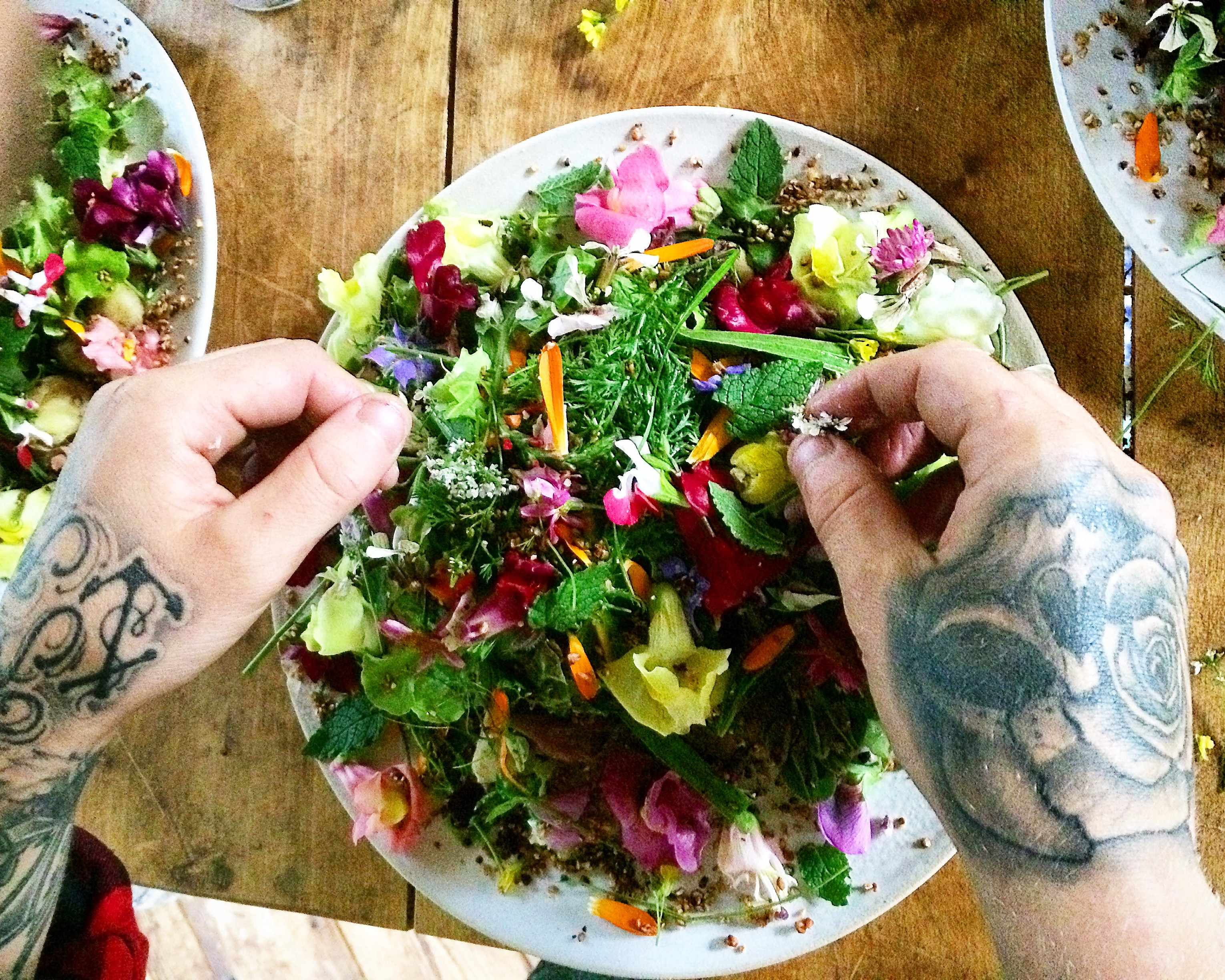Tattooed hands preparing a colourful flower salad