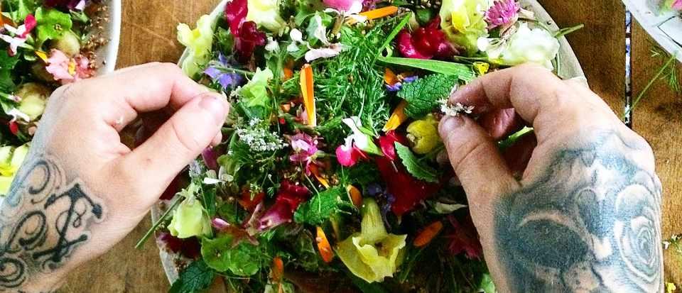 Tattooed hands preparing a colourful flower salad