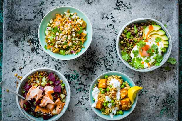 Four bowls of grains on a dark background