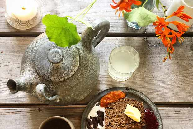 A flat lay of a stone teapot, a jar of orange flowers and a plate with rye bread and fruits