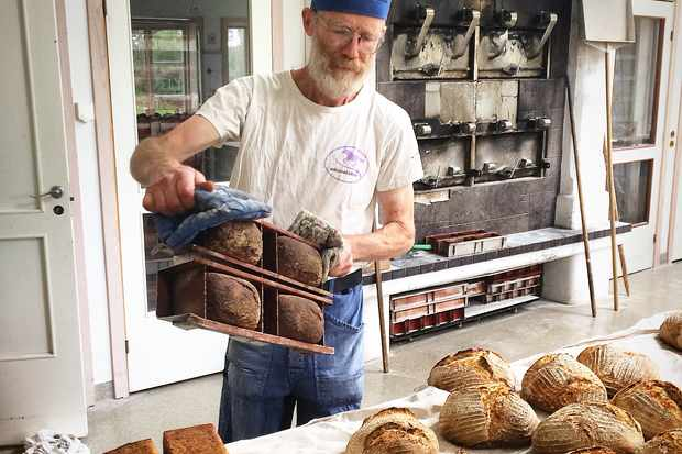 A man in a white t shirt getting loaves of bread out of an ancient iron oven