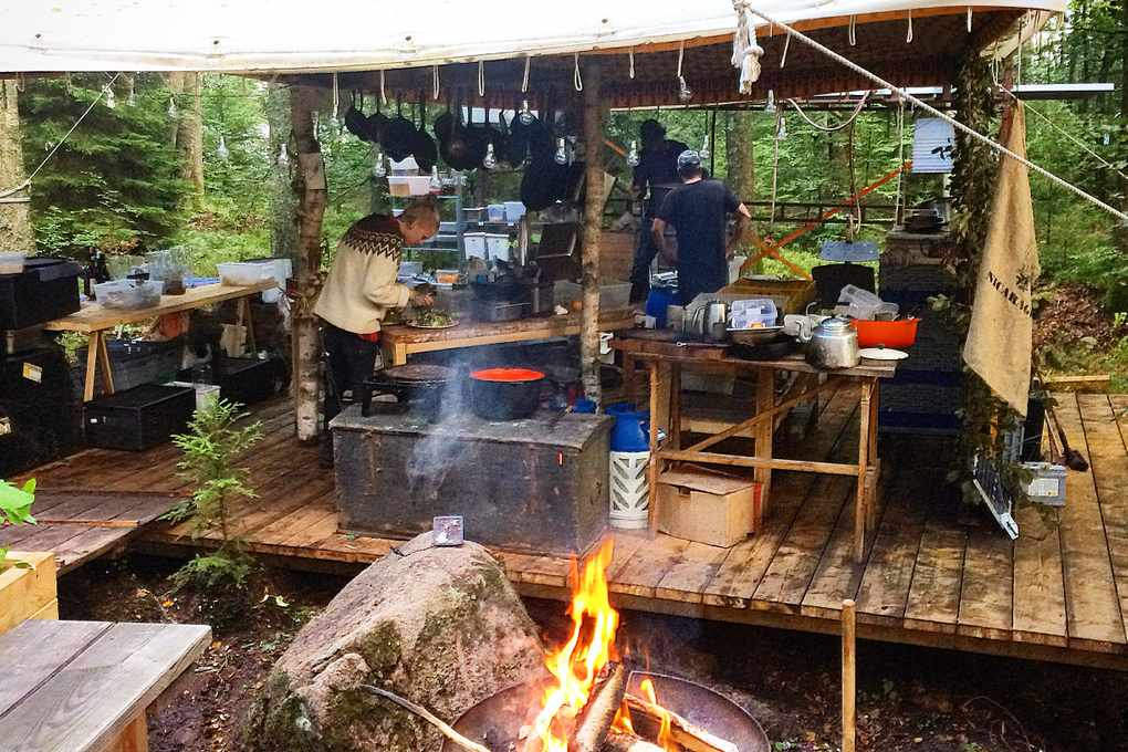 Fire pit with a kitchen in the background under a tent on a wooden platform