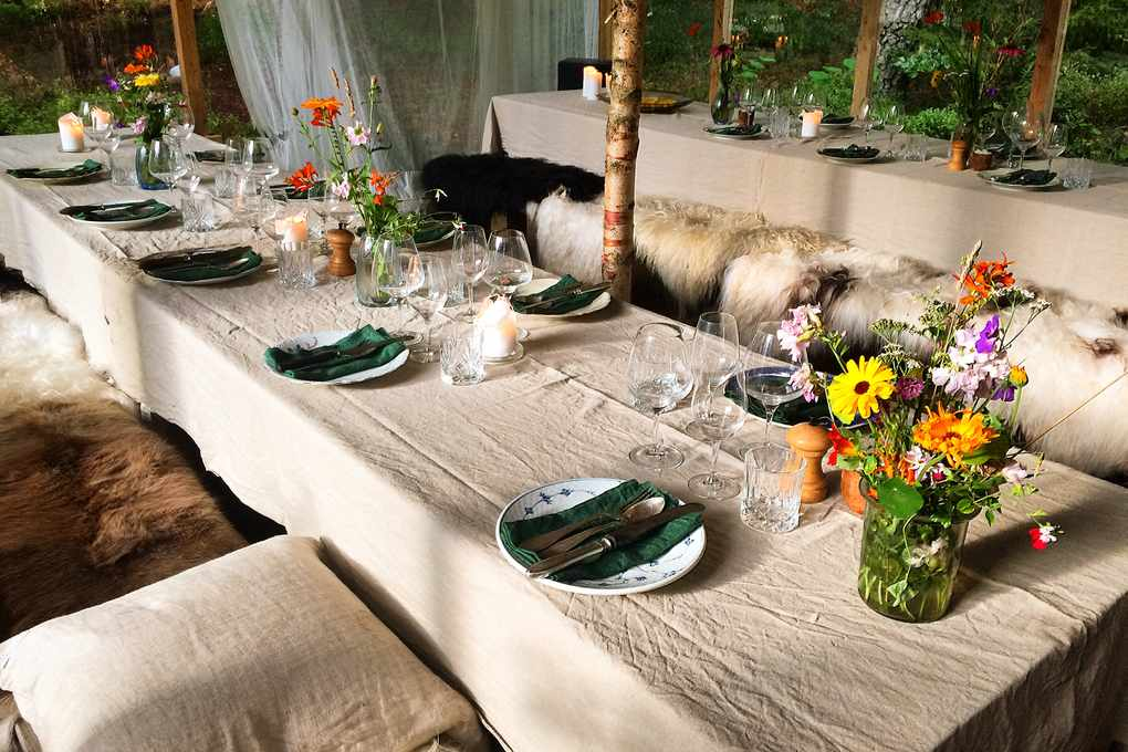Long tables with white table cloths decorated with flowers