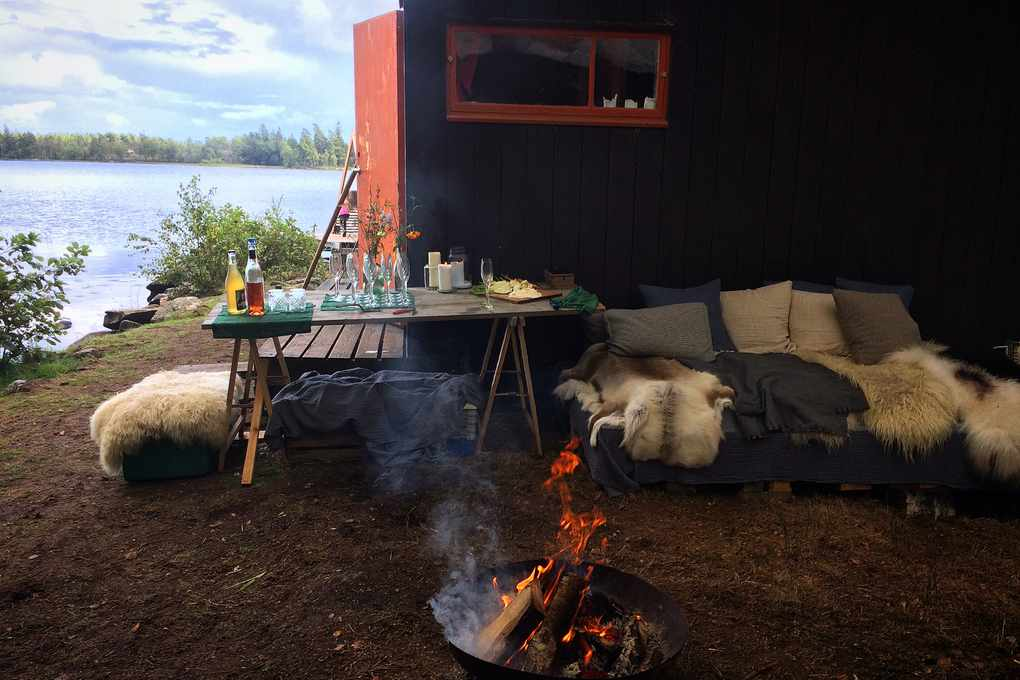 A cabin by the lake with a fire and sofas covered in fur rugs