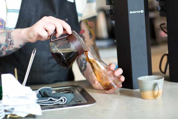 Man with tatto arm pouring coffee into a carafe