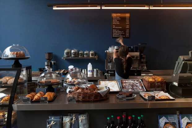 Counter filled with pastries with a dark blue wall behind