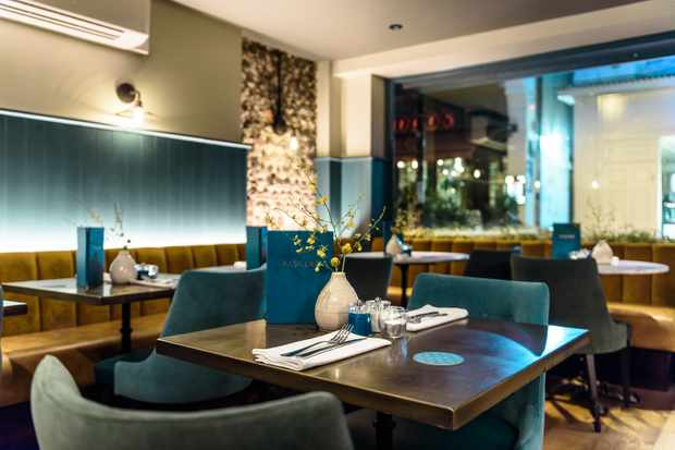Pascere Brighton restaurant with blue teal chairs, brass tables and mustard banquettes