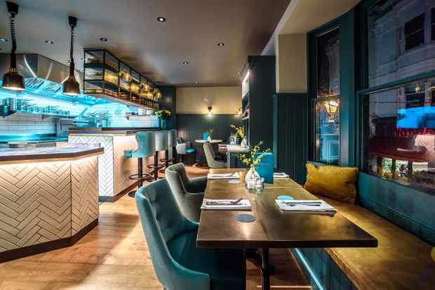 Pascere Brighton Upstairs with a white tiled counter, brass tables and blue teal chairs