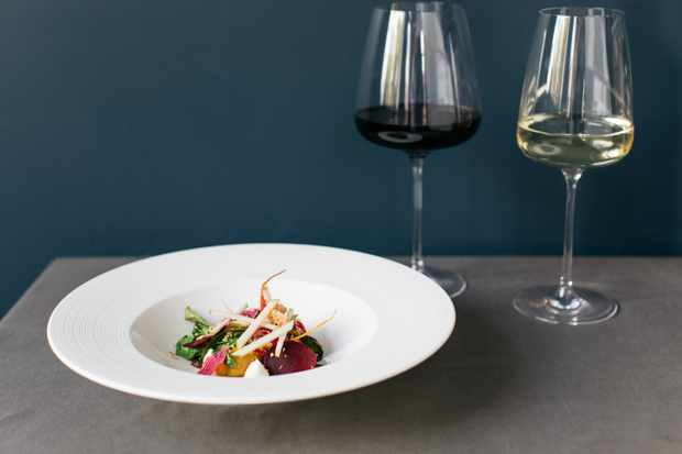 A plate of baby beetroots with a glass of white wine and a glass of red wine