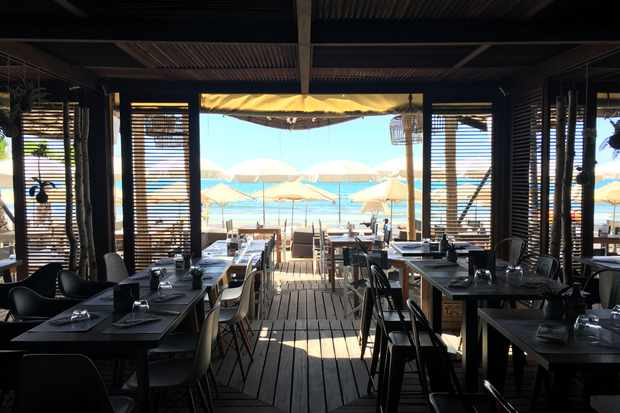 Effet mer interior - wooden tables and chairs with a view of the beach