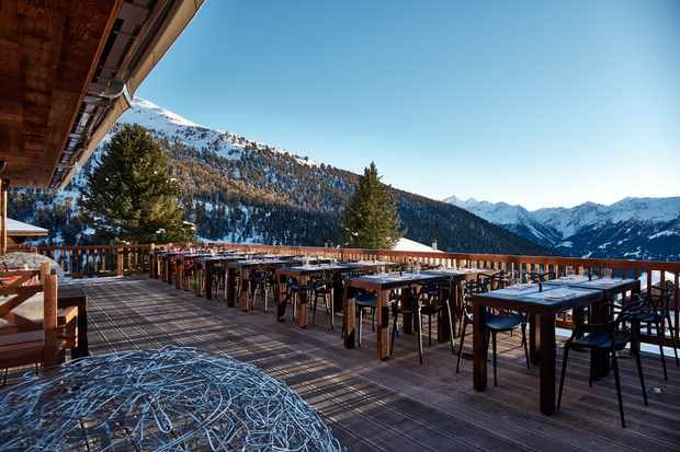 The outdoor terrace with wooden tables and snowy views at the Chandolin Hotel