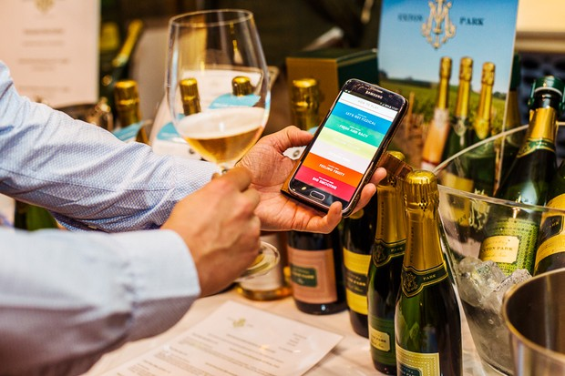 Winchester Wine Festival, man holding glass of white wine and his phone. There's an app open on his phone with different categories of wines on. Bottles of wine are on the table around him
