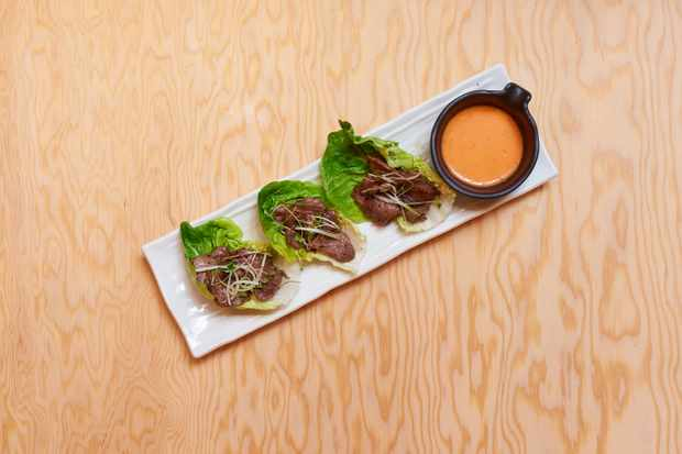 Pieces of cooked beef in green lettuce cups with an orange-coloured salsa