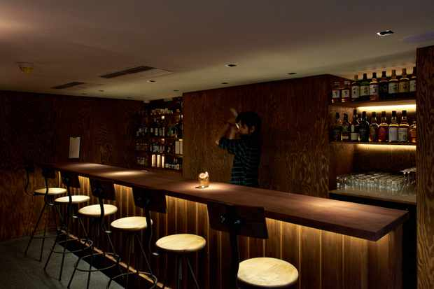 Darkly lit bar with stools and spotlights