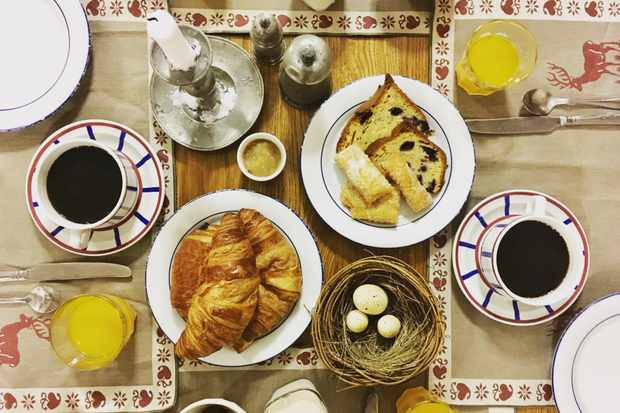 A breakfast spread with croissants, juice and fruit loaf