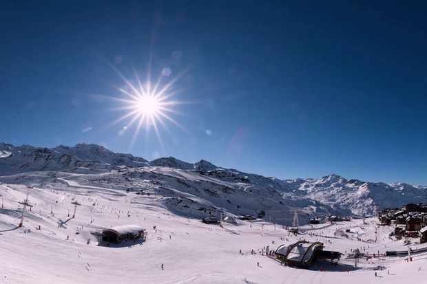 View of the slopes at F°7 hotel, Val Thorens, the sun is shining low in the bright blue sky, the snow is thick and white