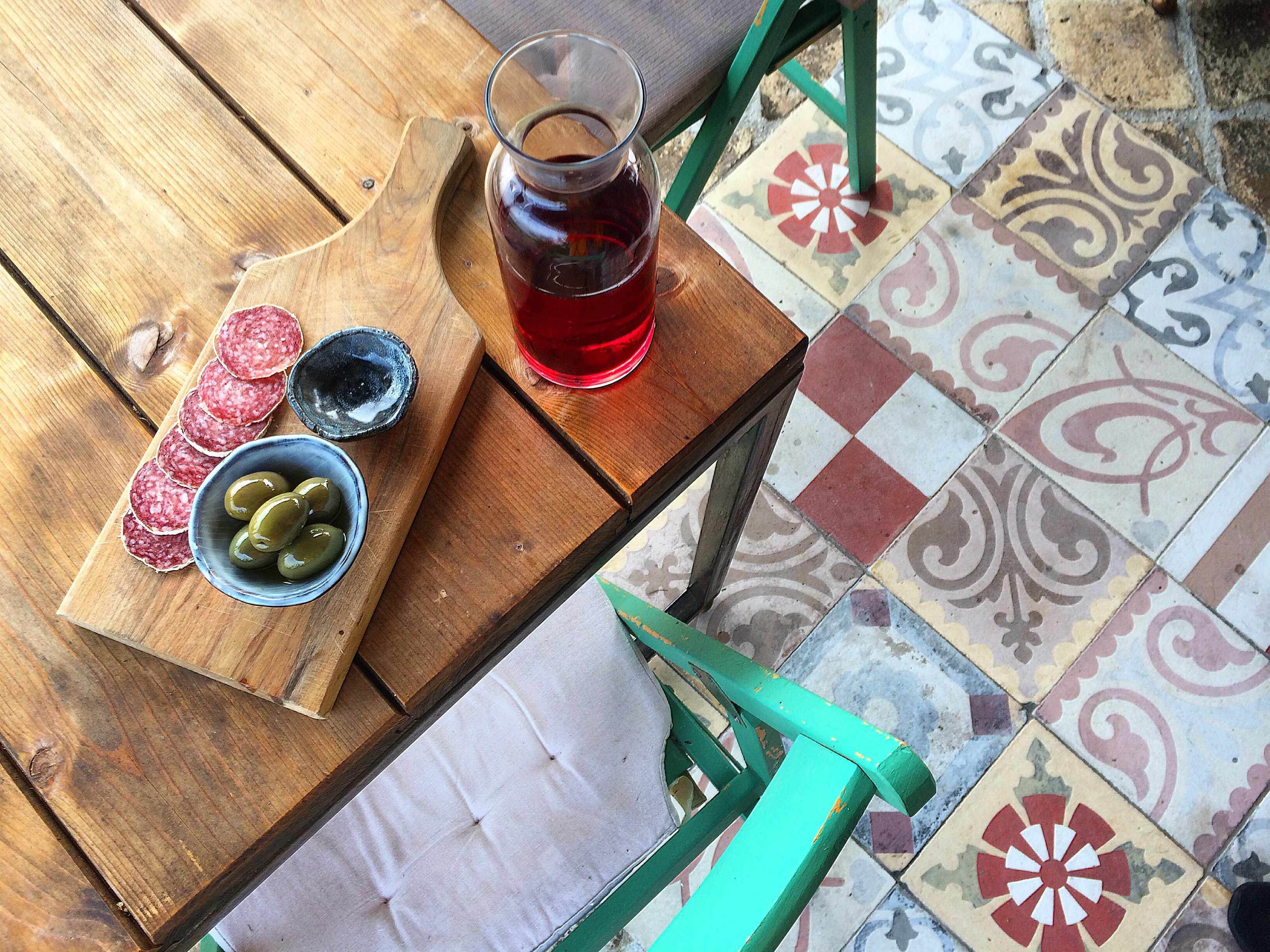 A carafe of rose wine with a plate of charcuterie with a tiled floor beneath
