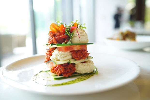 A white plate with layers of courgette, tomato and red and white fillings