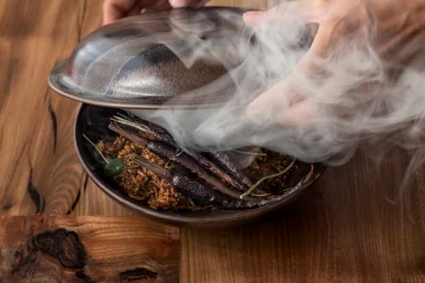 Lid being taken of a steel dish with smoke coming out