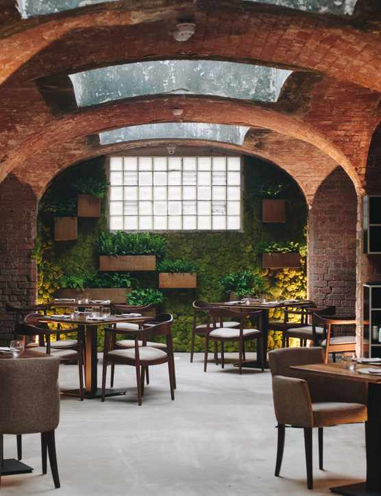 The inside of Alchemilla in Nottingham. Exposed brick work arches, roof top windows and dark wooden tables and chairs