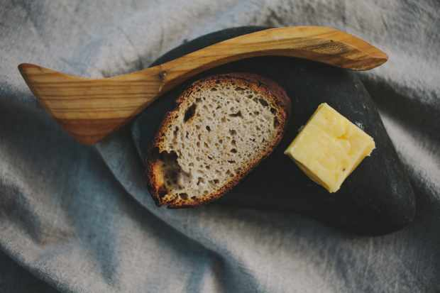 Sourdough and cultured butter served on a cold stone with a wooden butter slice on a linen napkin at Alchemilla