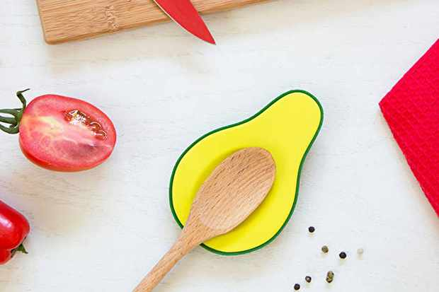 A yellow spoon rest shaped like an avocado with a green outline. There is a wooden spoon resting on the spoon rest