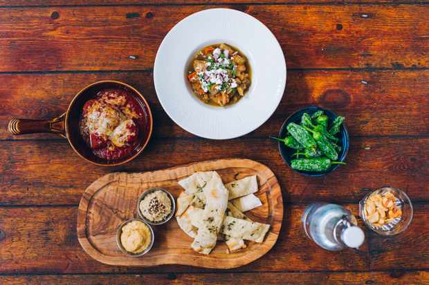 Food at Baresca Nottingham. On a wooden table there is a bowl of green patron peppers, a wooden board topped with flatbreads and two dips, a bottle of water and a bowl of stew