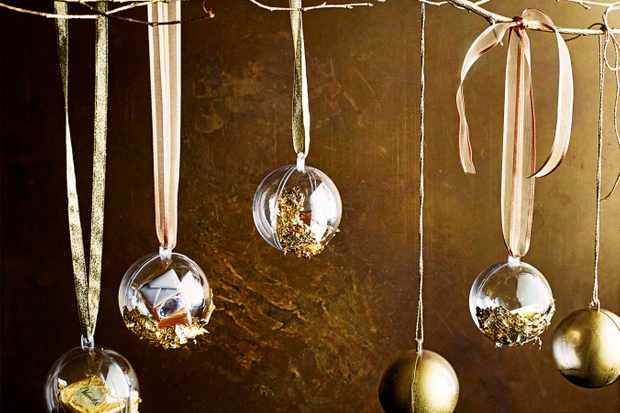 Gold baubles hanging with ribbon on a gold background