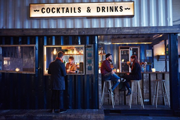 Indoor Copenhagens Street Food Market, the illuminated sign says Cocktails and Drinks and people are stood at the bar