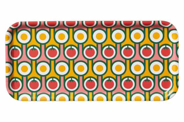 A long tray with a repeating print of yellow and red circles that represent eggs and tomatoes