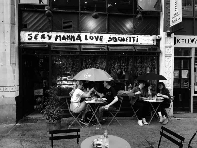 Sexy mamma loves spaghetti - a black and white photo of the outside of sexy mamma loves spaghetti. There is a sign with sexy mamma loves spaghetti written on it, and people sit on tables outside holding on umbrella over their heads