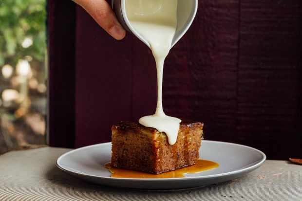 Sticky toffee apple cake with custard at The Ethicurean. A plate is topped with a piece of the cake and a hand is holding a jug with custard pouring from it